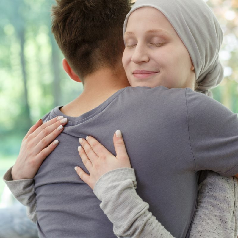 Female cancer patient getting hug from friend