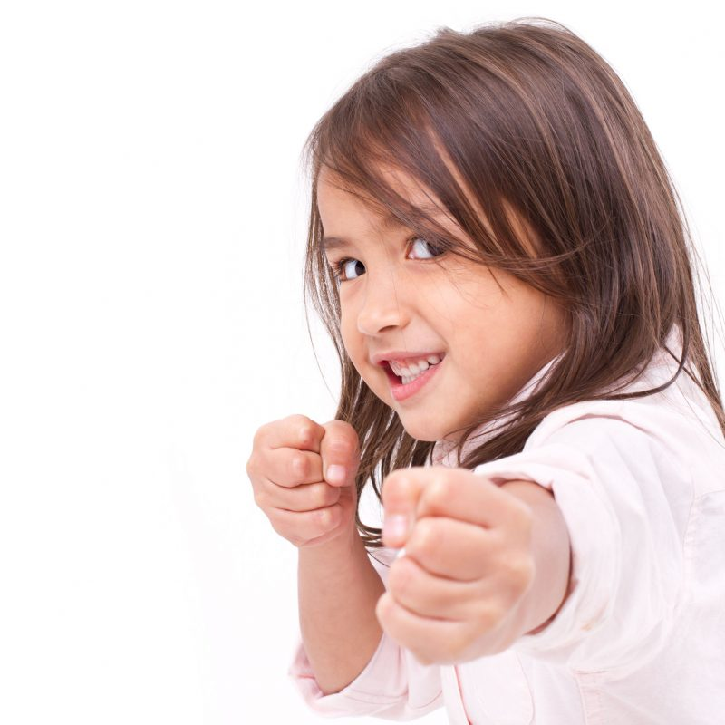 Young girl smiling in self-defense pose