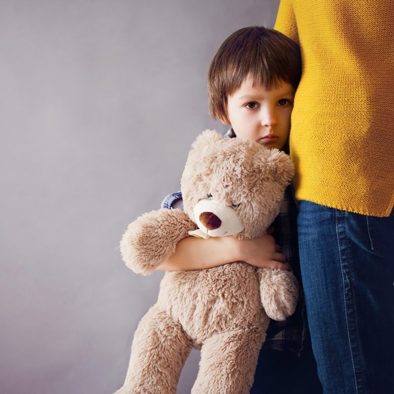 Young boy holding teddy bear and snuggling next to his mother