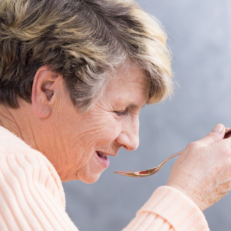 Older woman eating soup